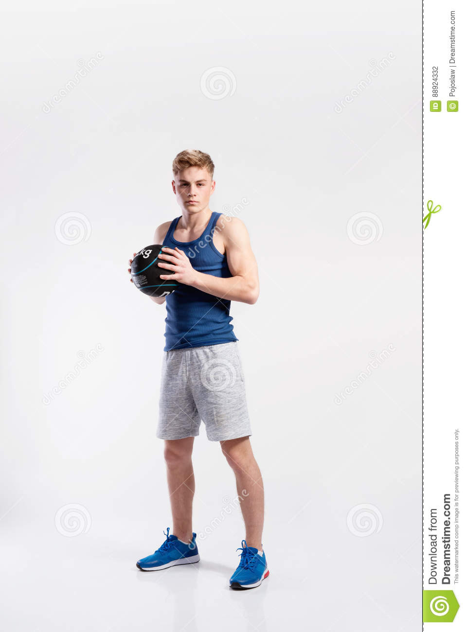 306bf726fef73 Handsome hipster fitness man in blue tank top shirt and gray shorts holding  medicene ball. Studio shot on gray background.