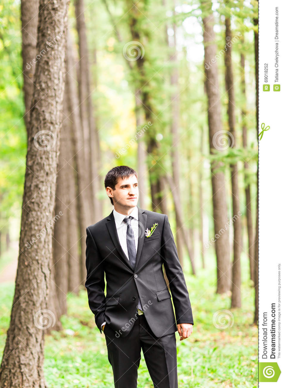handsome groom in suit on the nature male portrait outdoors man is