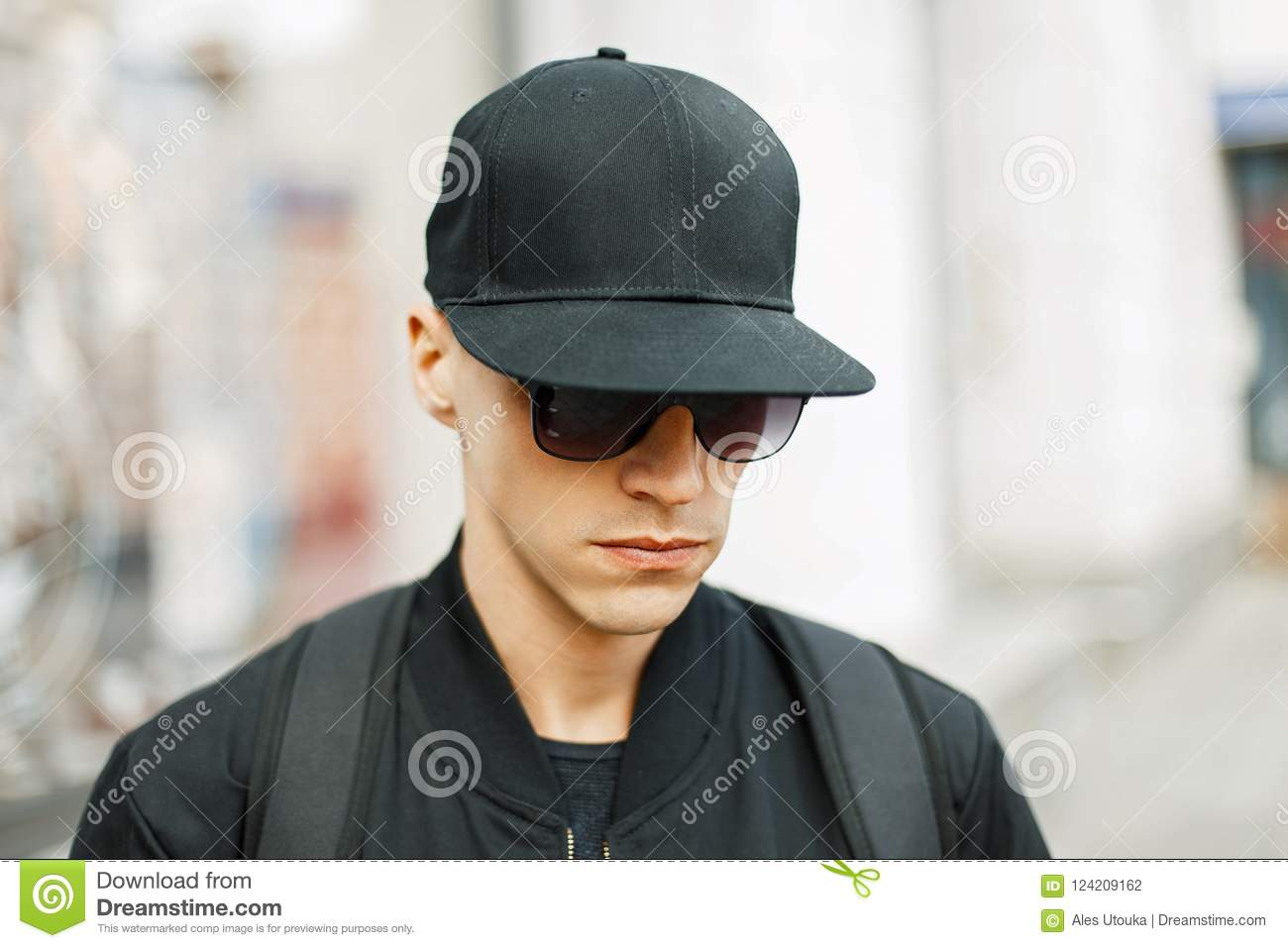 Handsome Guy In A Black Baseball Cap And Stylish Black Clothes Stock ... 73ea8dbc64e