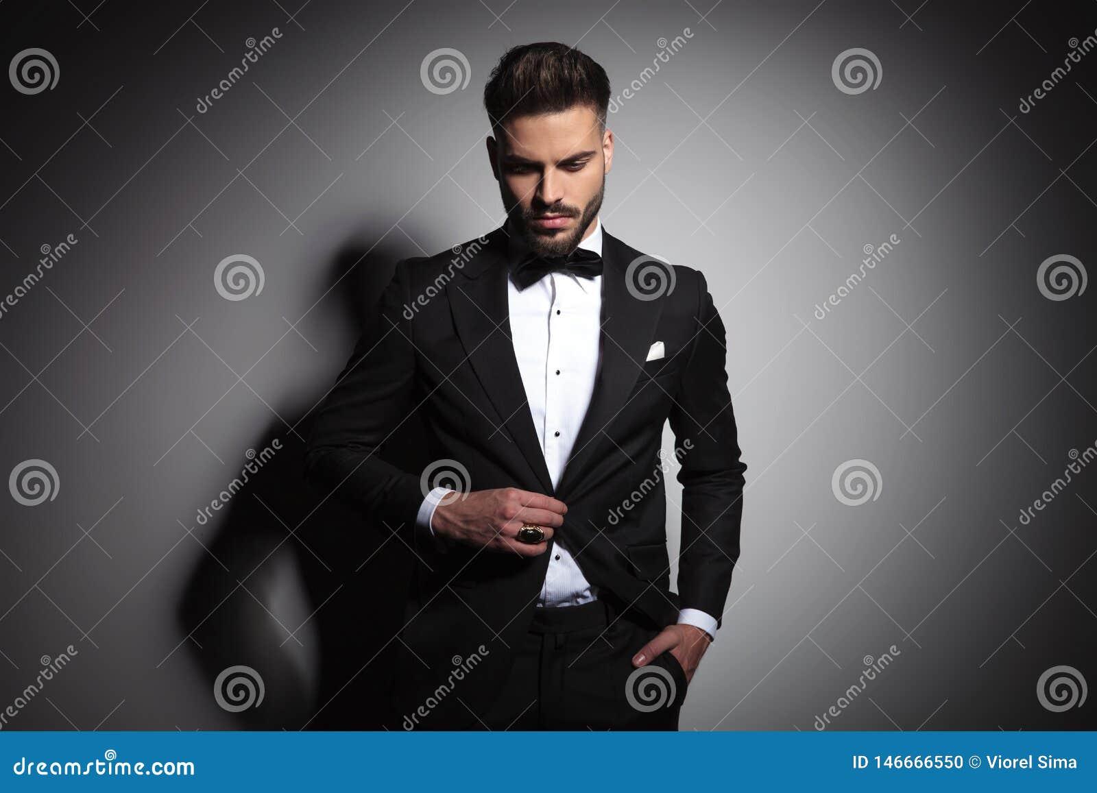 handsome guy in black tuxedo holding hand in pocket