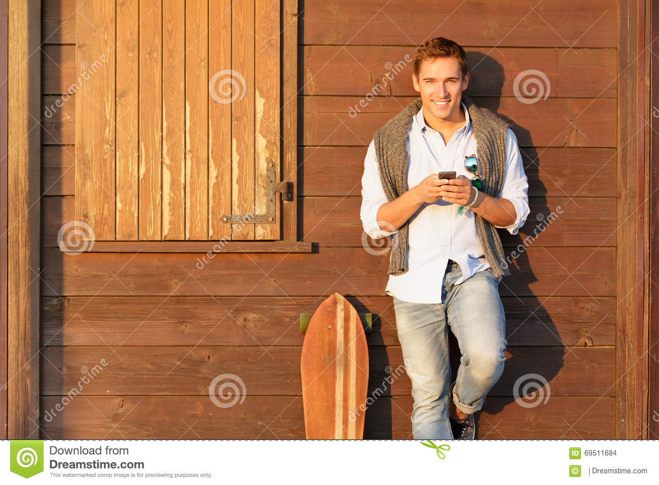 Handsome guy in four season outfit standing on brown wooden background and holding his smartphone - Smiling men in autumn clothes