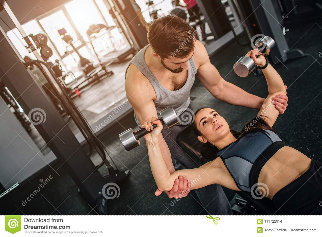 Handsome guy standing near his girlfriend and helping her to do exersices with a dumbbell. He is supporting her to make