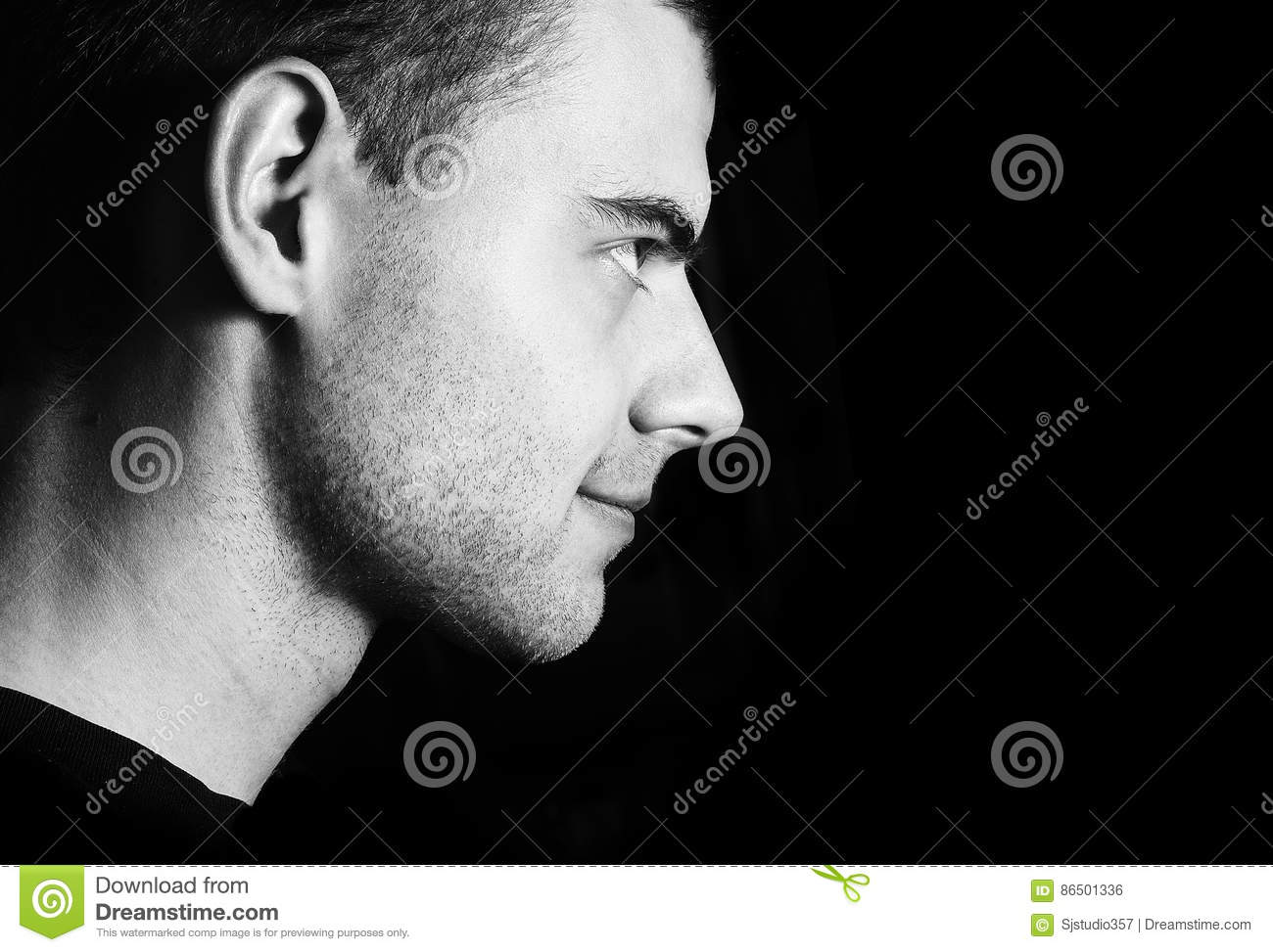 Handsome guy unshaven smiling dark portrait profile in low key black and white low key portrait of young