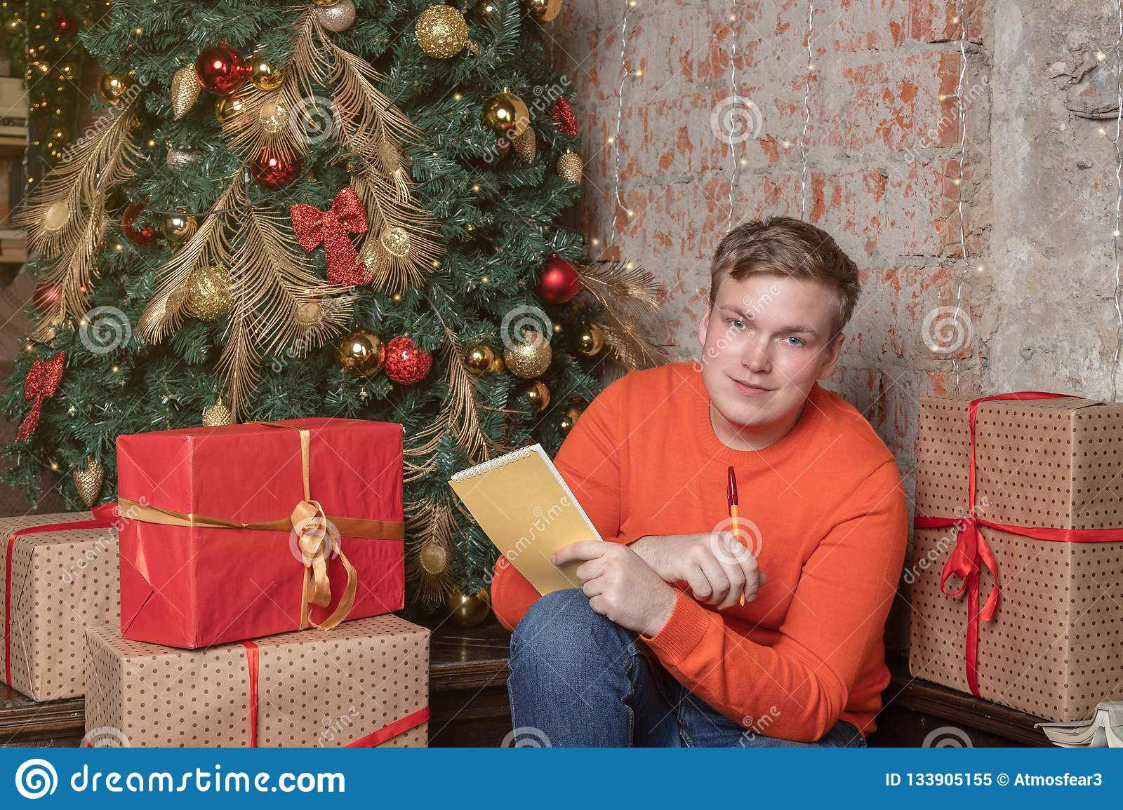 Handsome guy is writing a letter to Santa sitting under the tree surrounded by boxes of gifts. Christmas and gifts