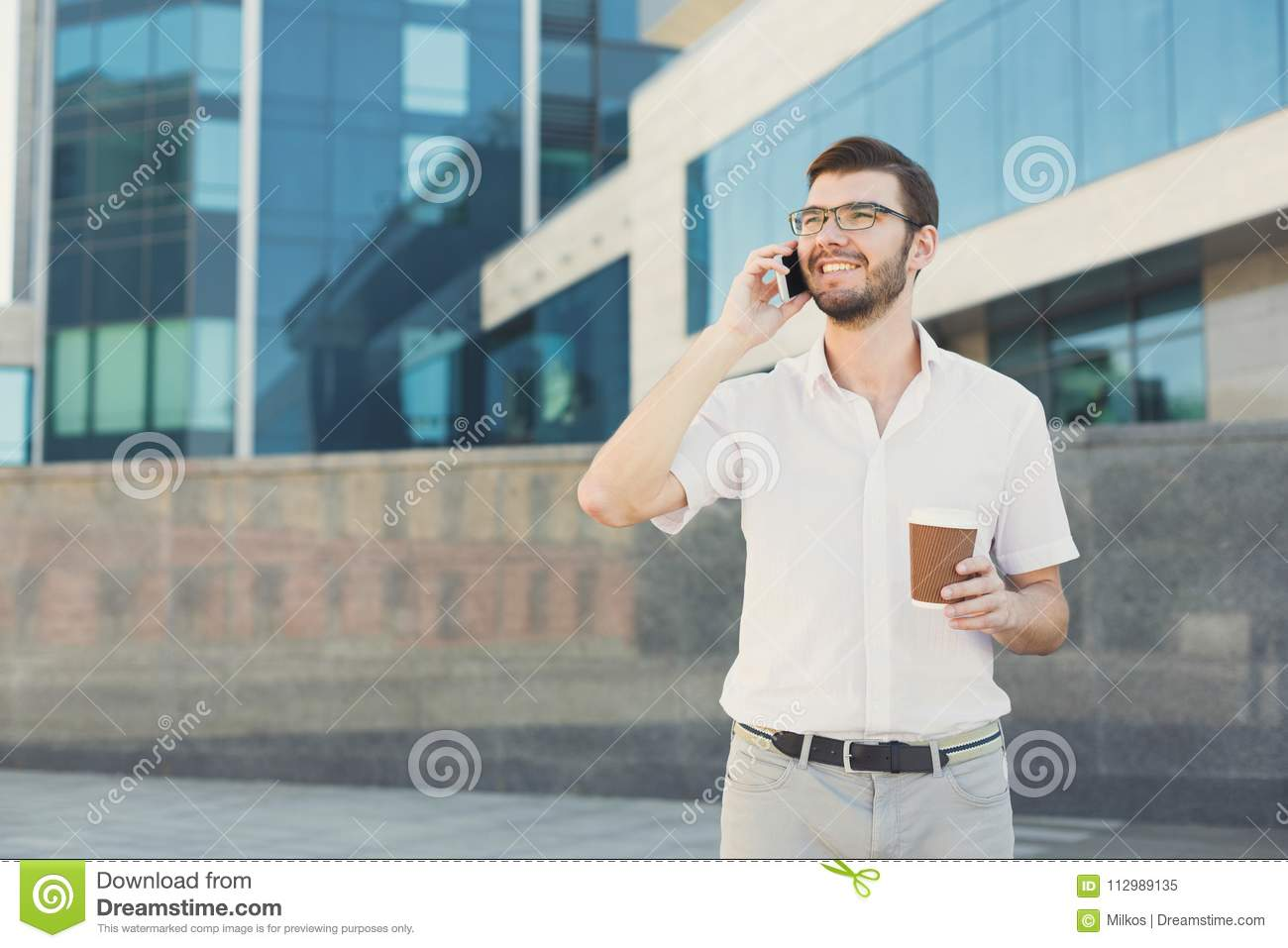 Young smiling businessman making a call outdoors