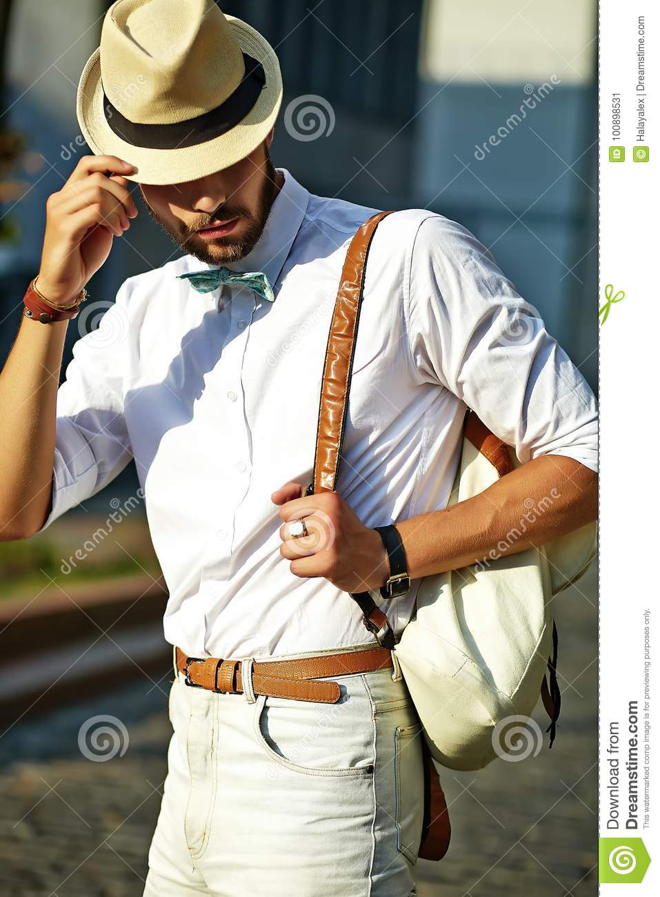 e1c61df7a134 Handsome hipster model man in stylish summer clothes posing on street  background in hat with bag