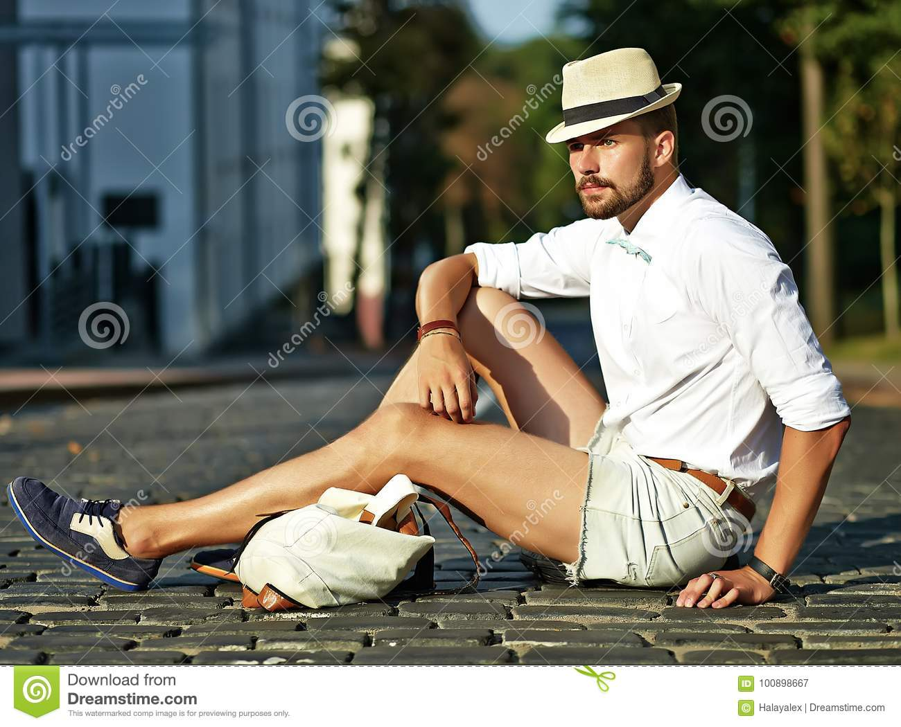 1a65c6f0136b Handsome hipster model man in stylish summer clothes sitting on street  background in hat with bag