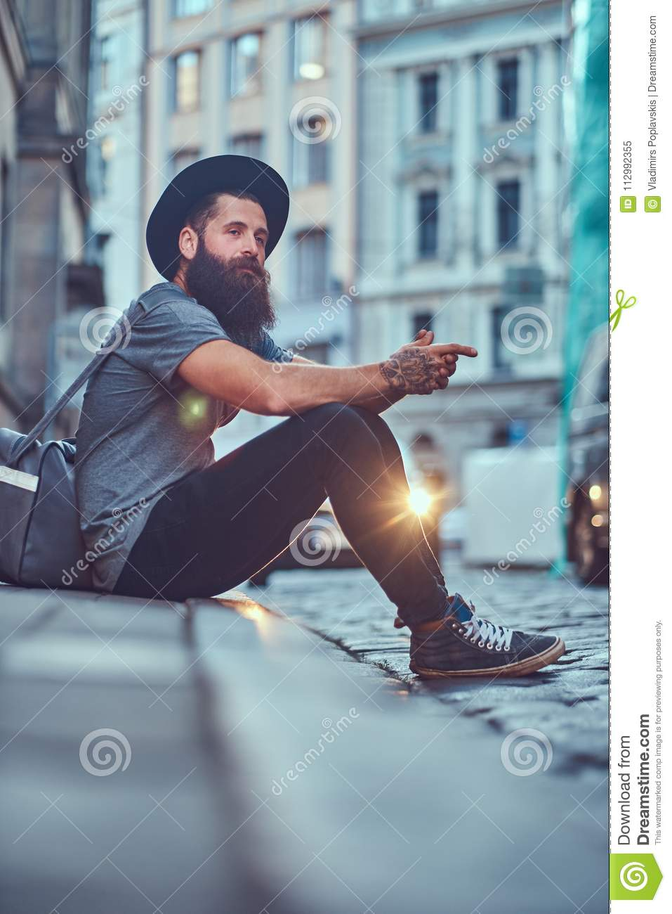 A handsome hipster traveler with a stylish beard and tattoo on his arms dressed in casual clothes with a bag, sits on