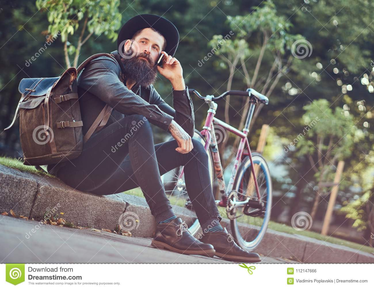 A handsome hipster traveler with a stylish beard and tattoo on his arms dressed in casual clothes and hat with a bag