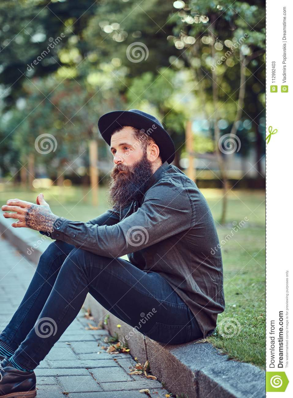 A handsome hipster traveler with a stylish beard and tattoo on his arms dressed in casual clothes and hat, sitting on
