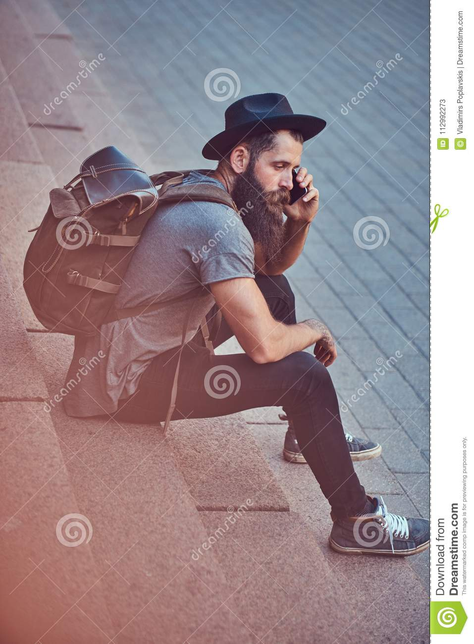 A handsome hipster traveler with a stylish beard and tattoo on his arms dressed in casual clothes, sitting on the steps