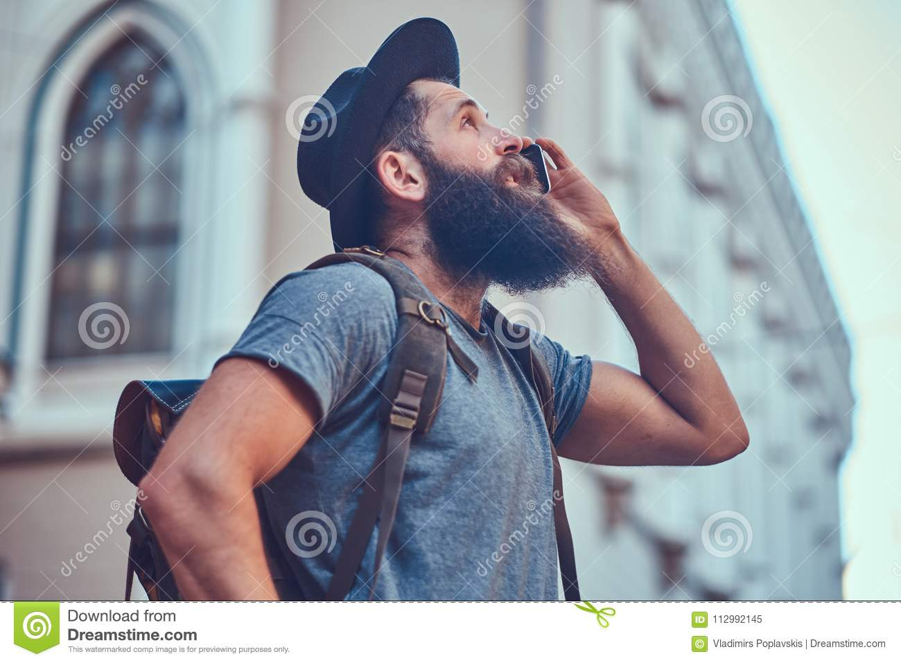 A handsome hipster traveler with a stylish beard and tattoo on his arms dressed in casual clothes, standing on the