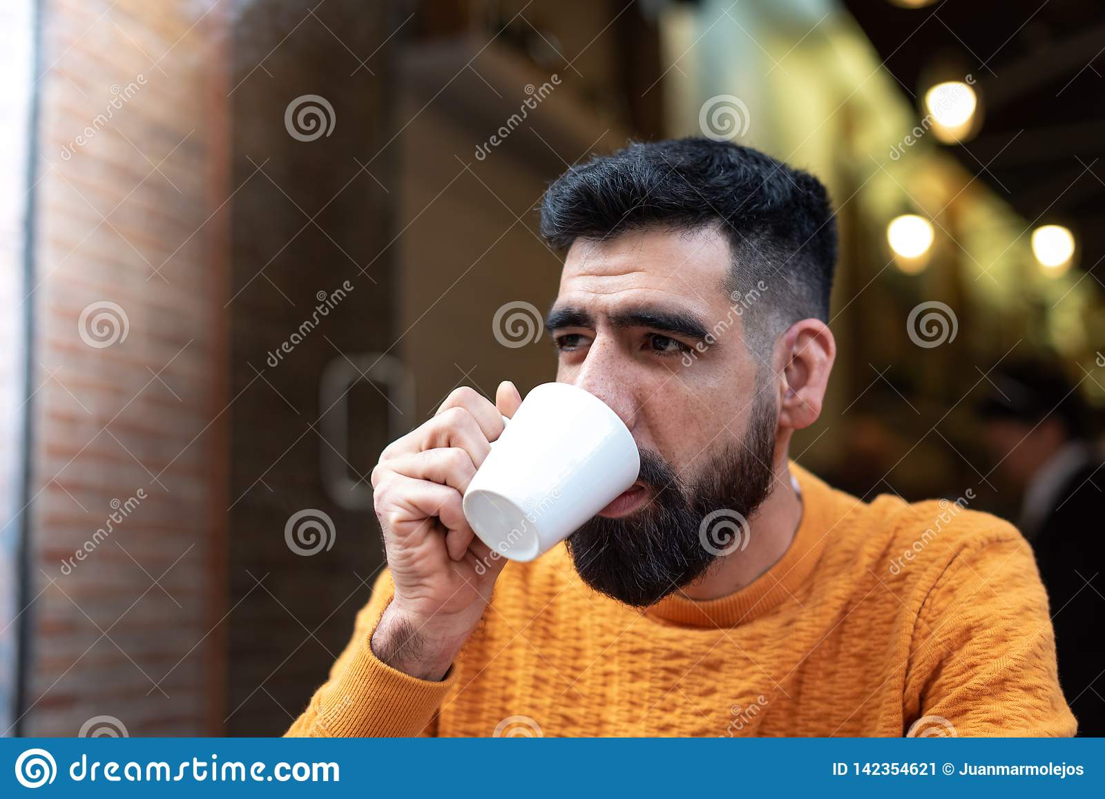 Handsome Latin Guy Drinking Coffee in a Terrace Cafe