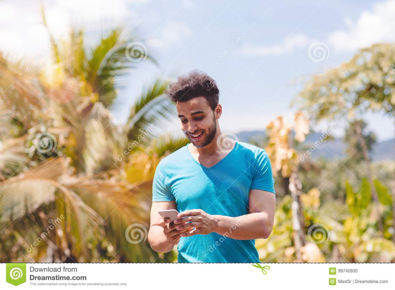 Handsome Latin Man Messaging With Cell Smart Phone Over Tropical Forest Background, Portrait Of Young Guy Chatting