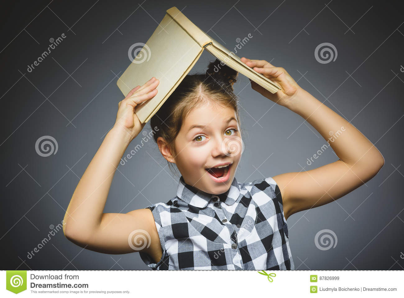 Handsome little girl with book smiling isolated on gray background