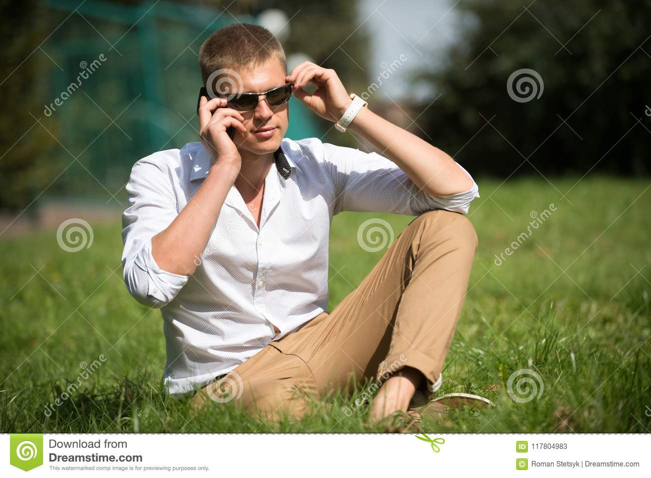 Handsome macho enjoy summer day. Businessman in sunglasses on sunny outdoor. Man relax on green grass. Fashion style and