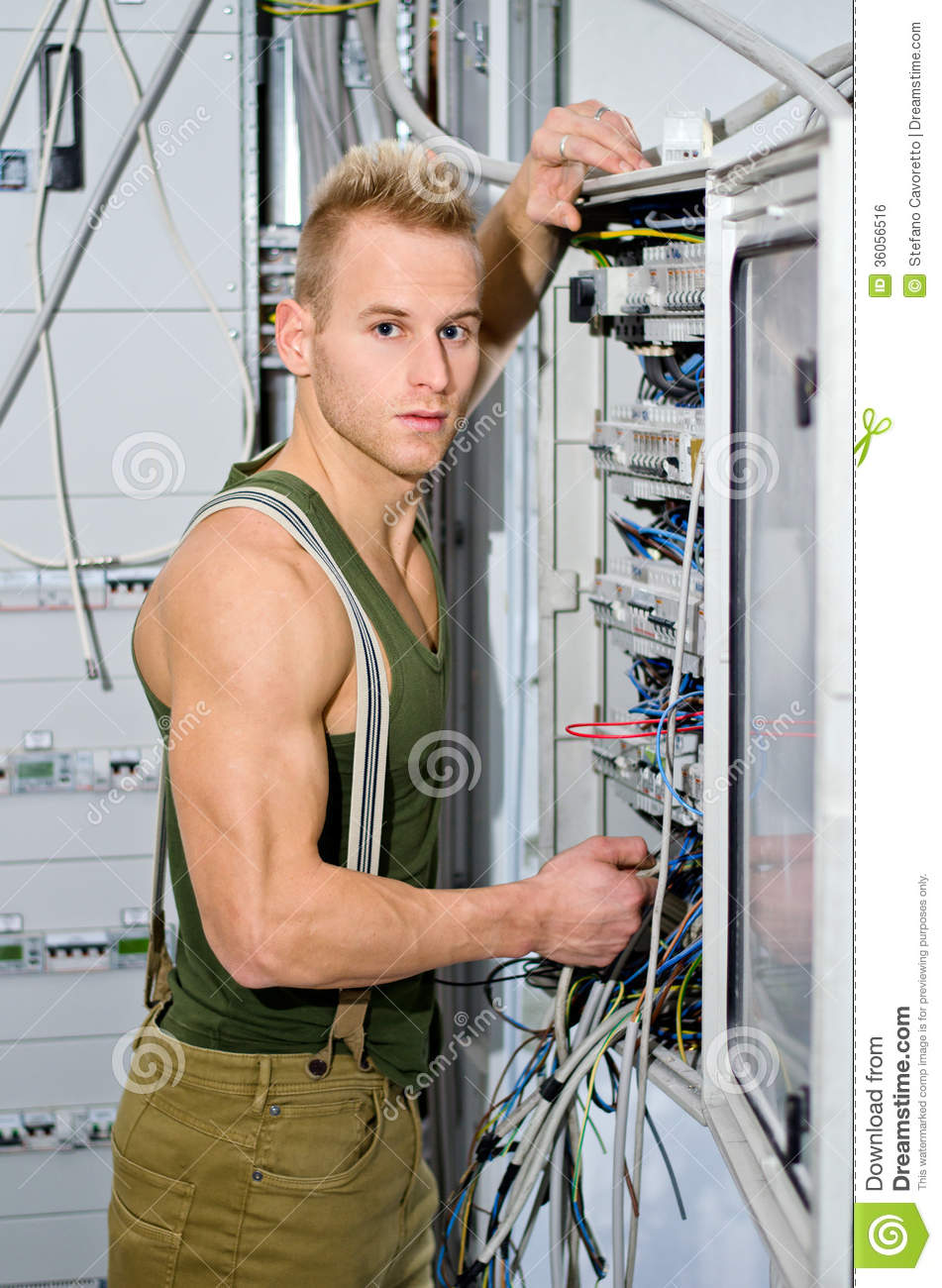 Handsome Male Electrician In Front Of Power Panel Royalty