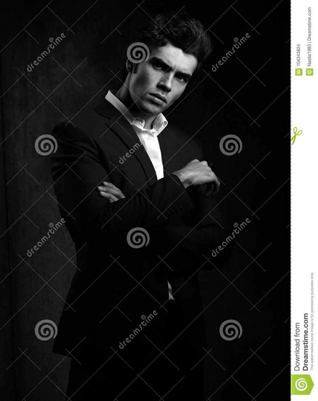 1f312a92 Handsome male model posing in fashion suit and white style shirt looking on dark  shadow background. Black and white portrait