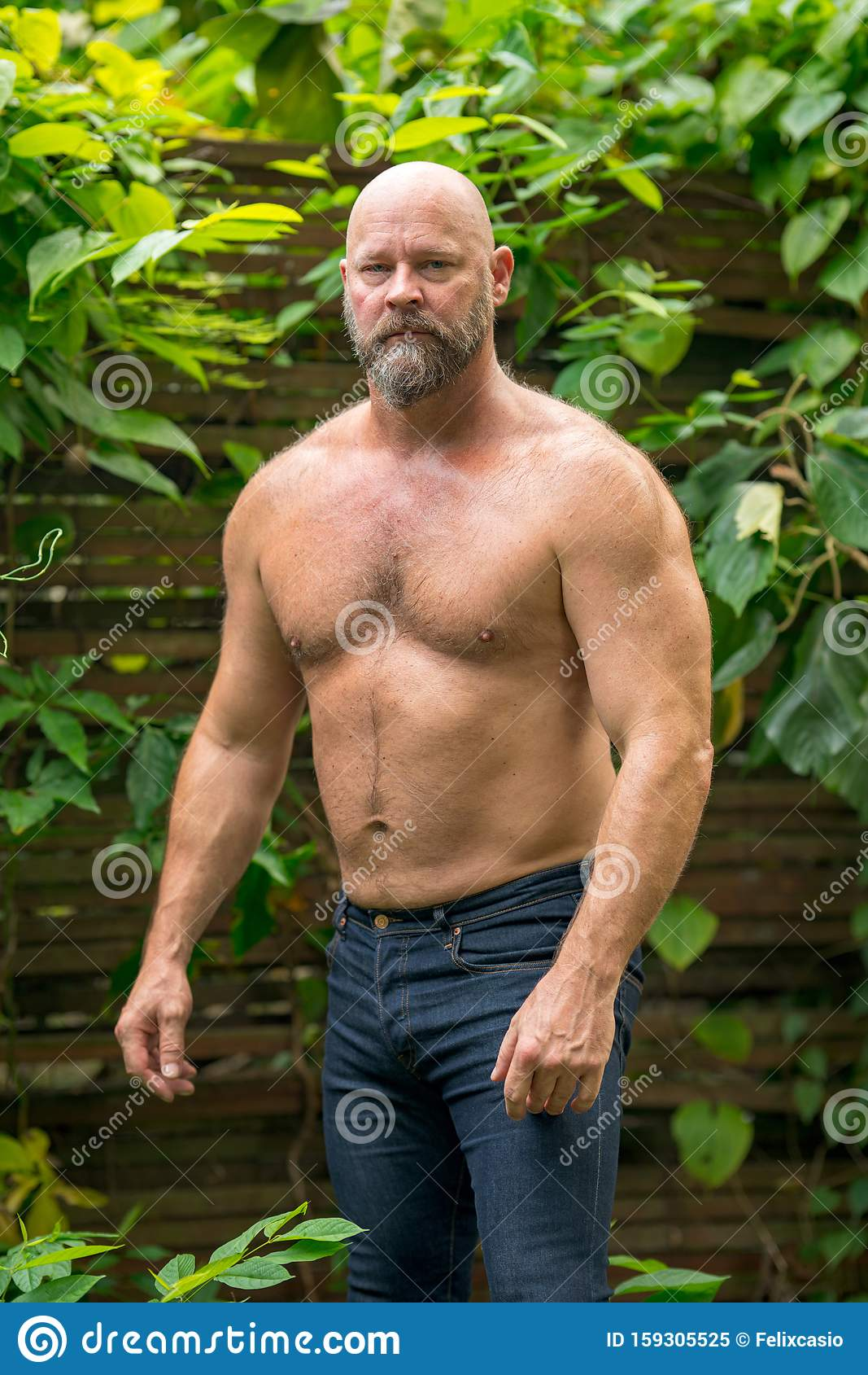 Handsome Male Model Posing Shirtless In The Garden