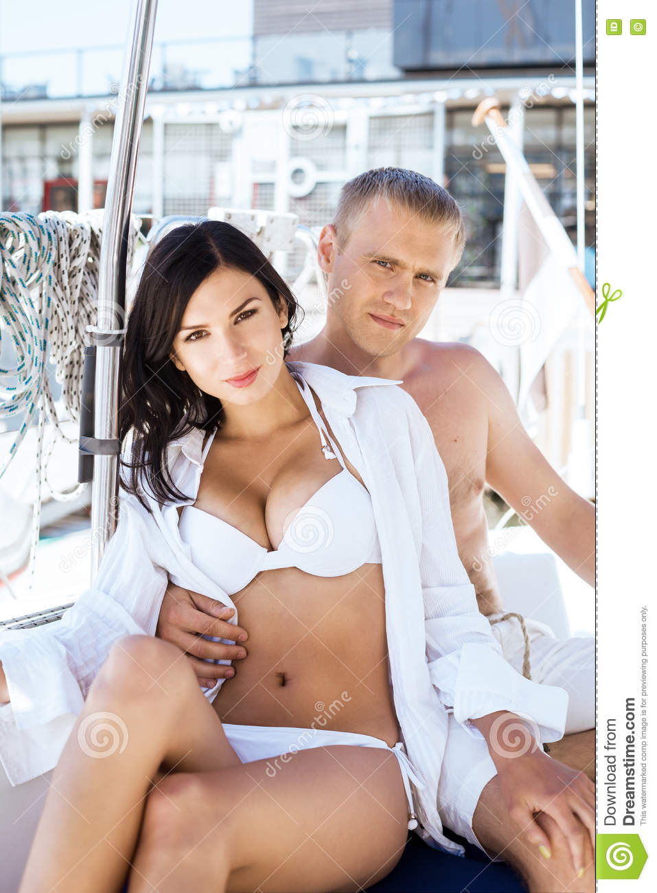 f7dd7321e8 Handsome and rich men and a beautiful and women in swimsuit relaxing on a sailing  boat