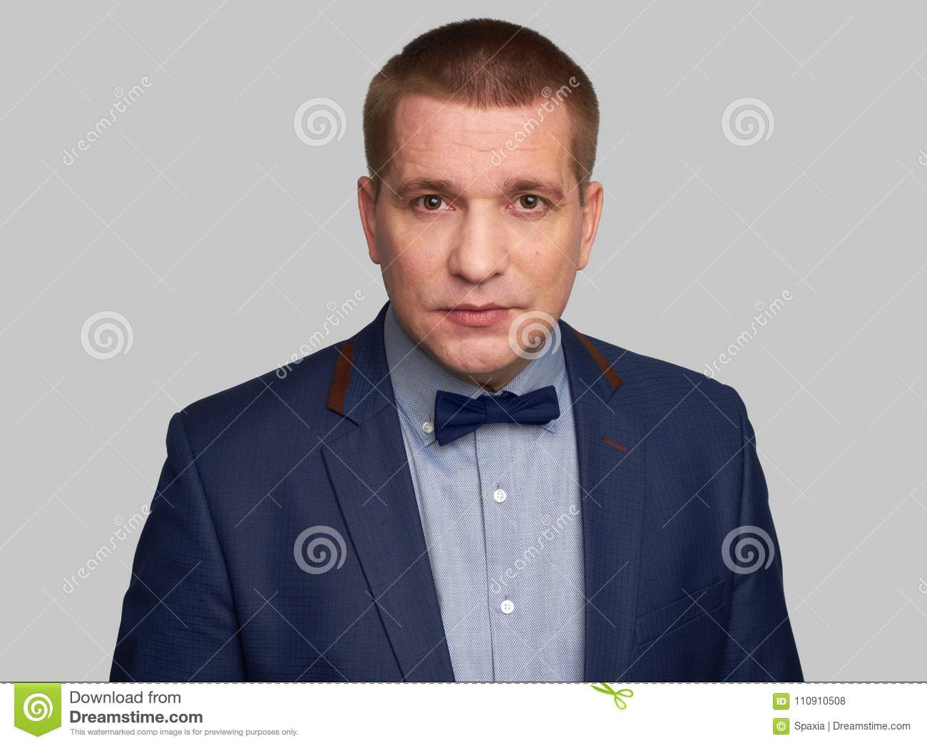 c5c8d0f7c160 Handsome man in blue suit and bow tie isolated on grey background. More  similar stock images