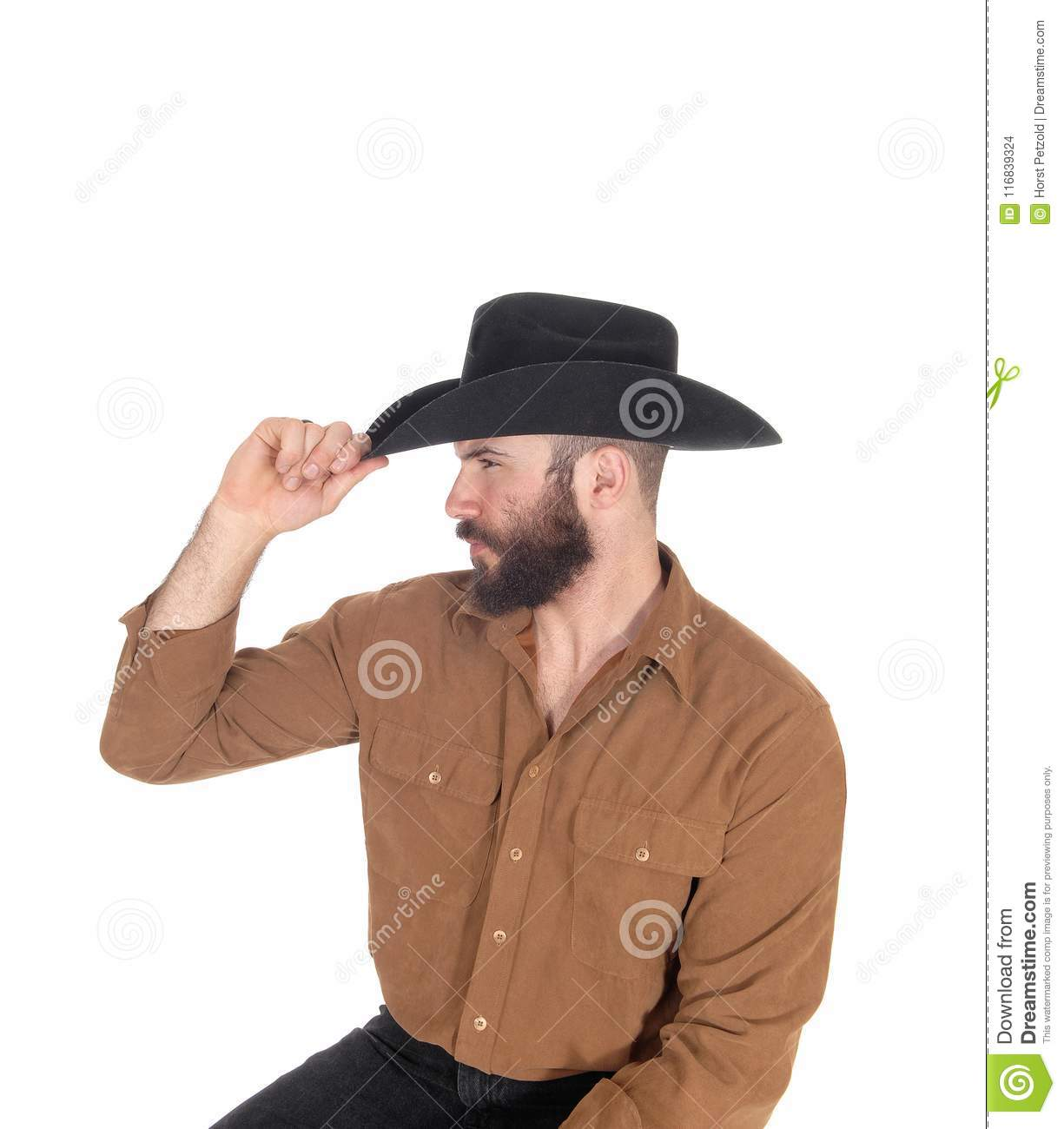 05c635bcf62 A young man sitting on a chair in profile wearing a black cowboy hat and  looking away