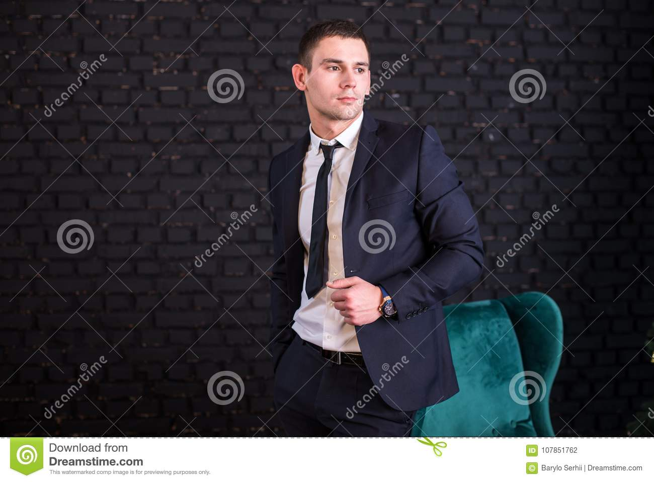 Handsome man in a business suit against a black brick wall, model photo. Succesful fashionable man