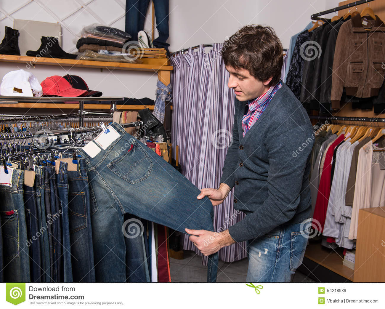 Handsome Man Choosing Jeans During Shopping Stock Photo - Image ...
