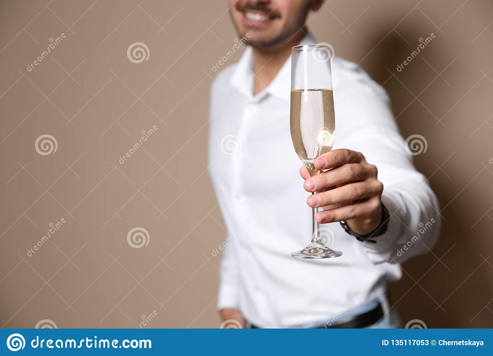 Handsome man with glass of champagne on color background, closeup.
