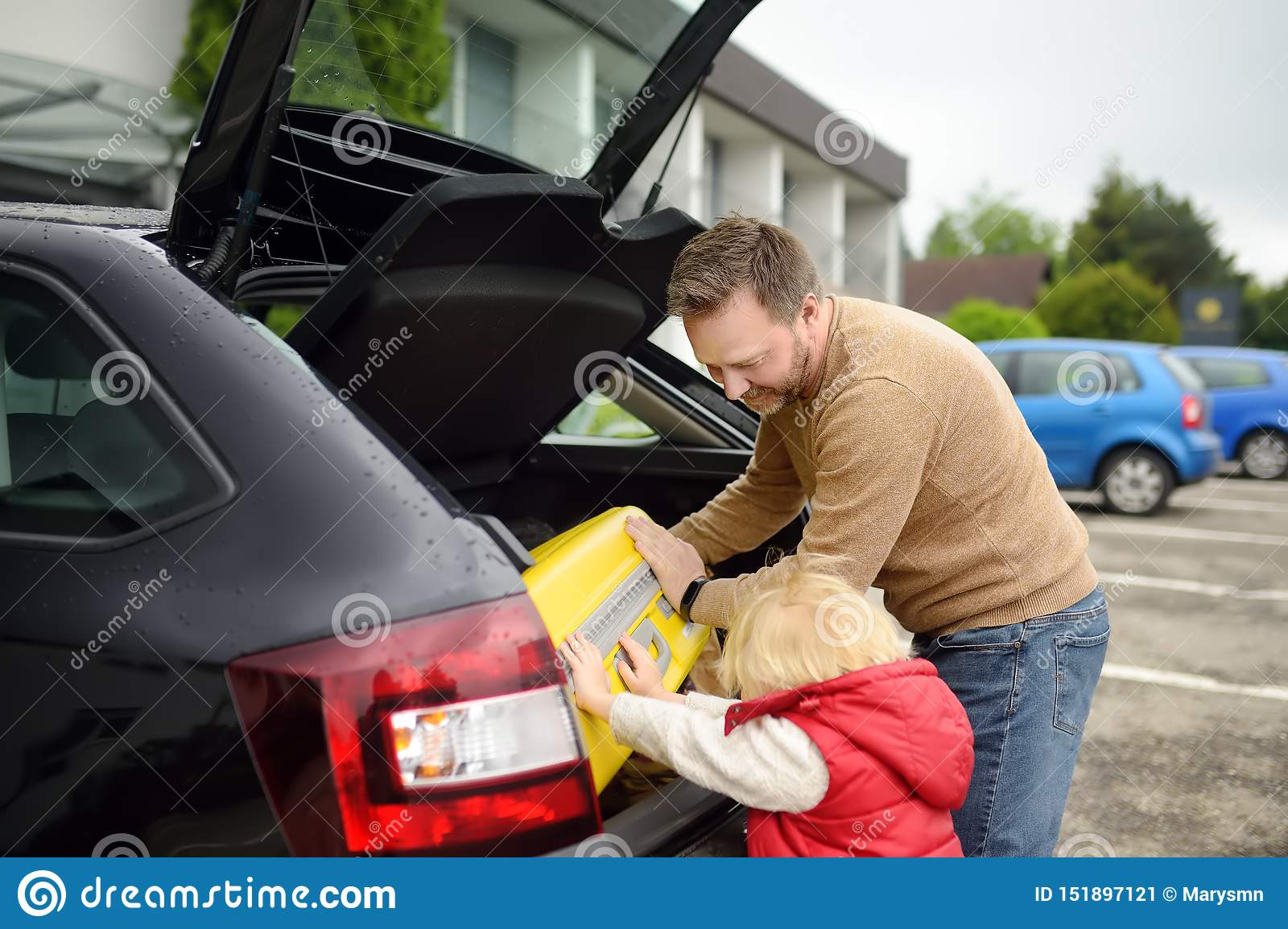 Handsome man and his little son going to vacations, loading their suitcase in car trunk. Automobile trip in the countryside.