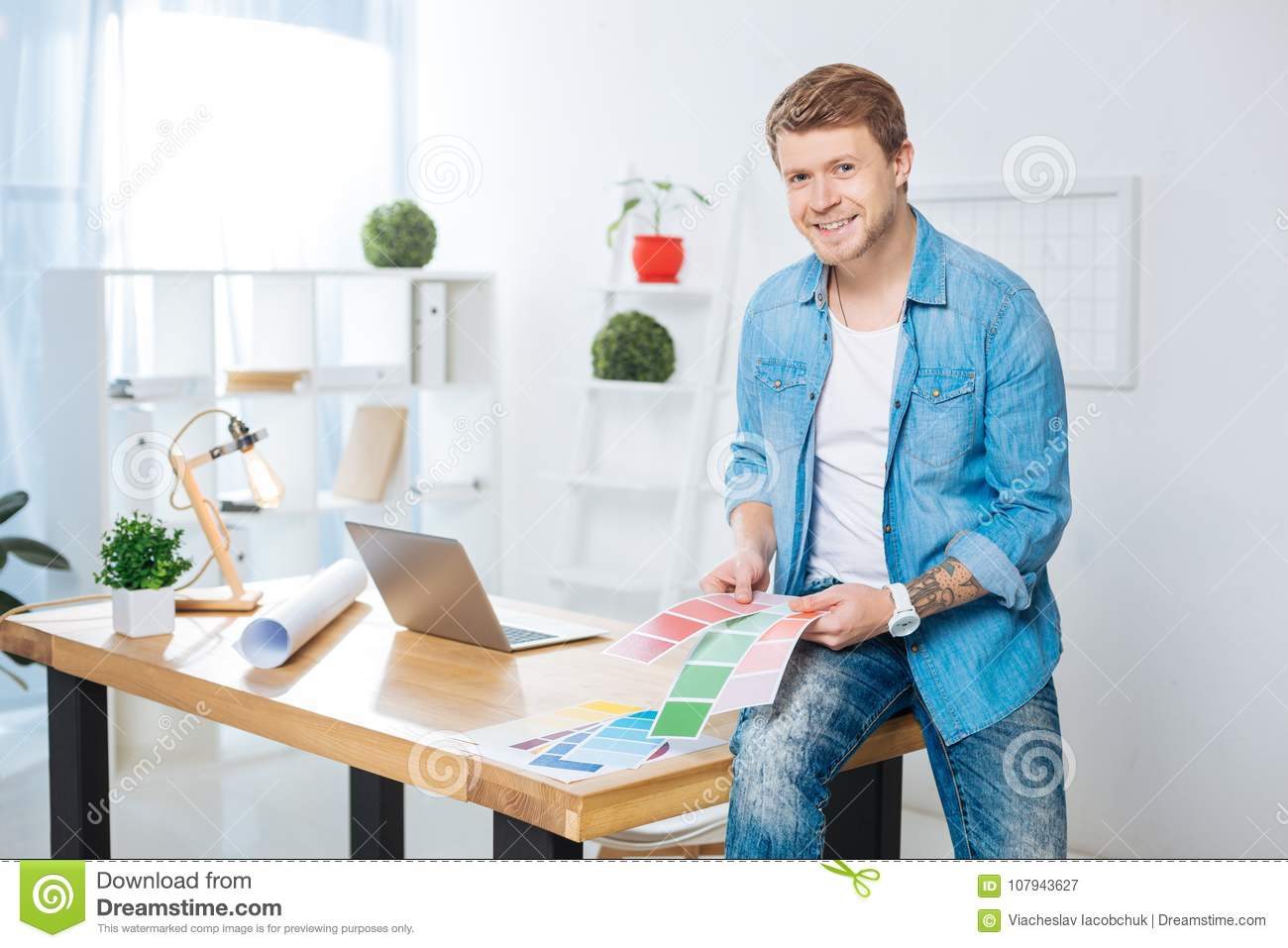 Handsome man holding color palettes and smiling