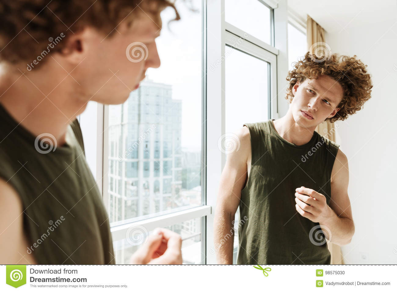 handsome man looking at mirror stock photo image of confident