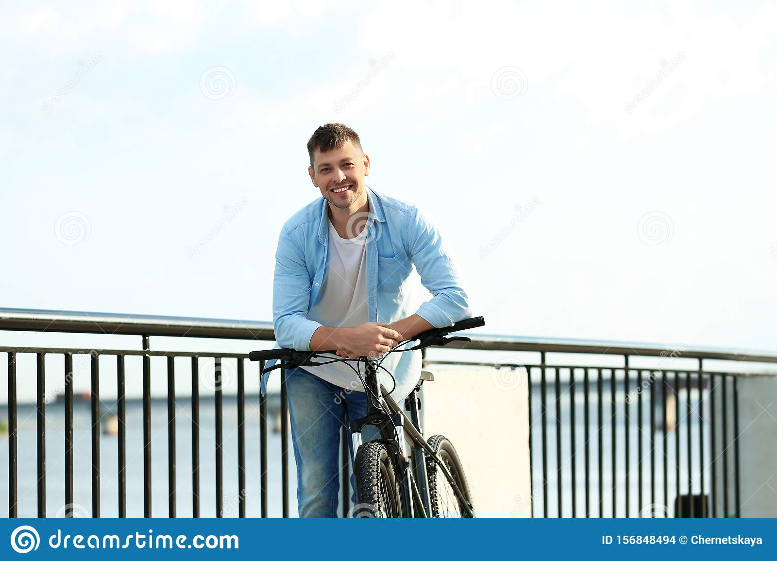 Handsome man with bicycle near river