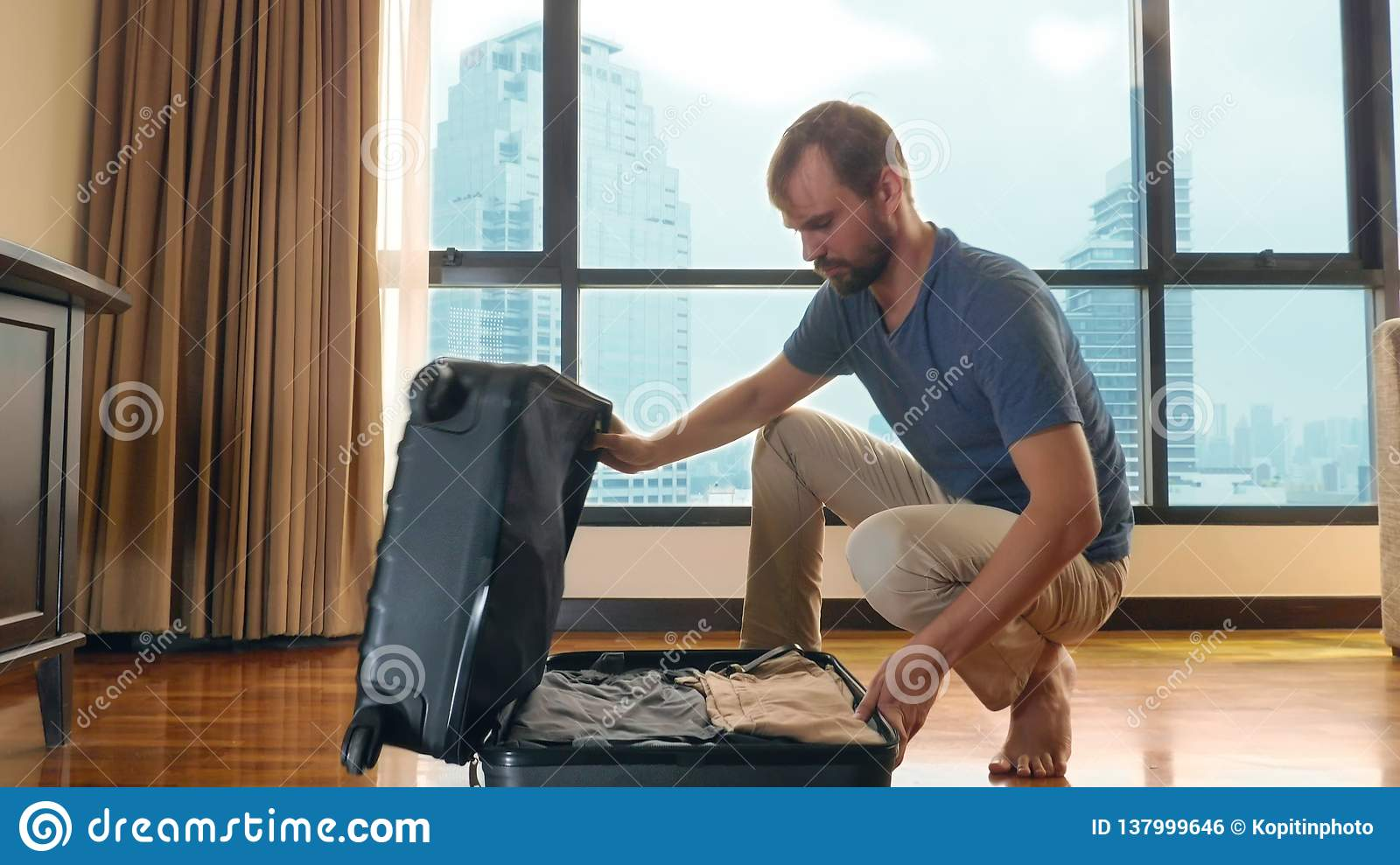 Handsome man packs a suitcase in a room with a panoramic window overlooking the skyscrapers