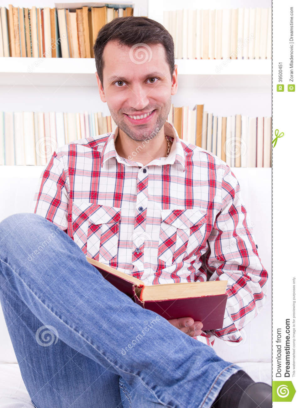 handsome man relaxing at home on a sofa in the living room reading a book