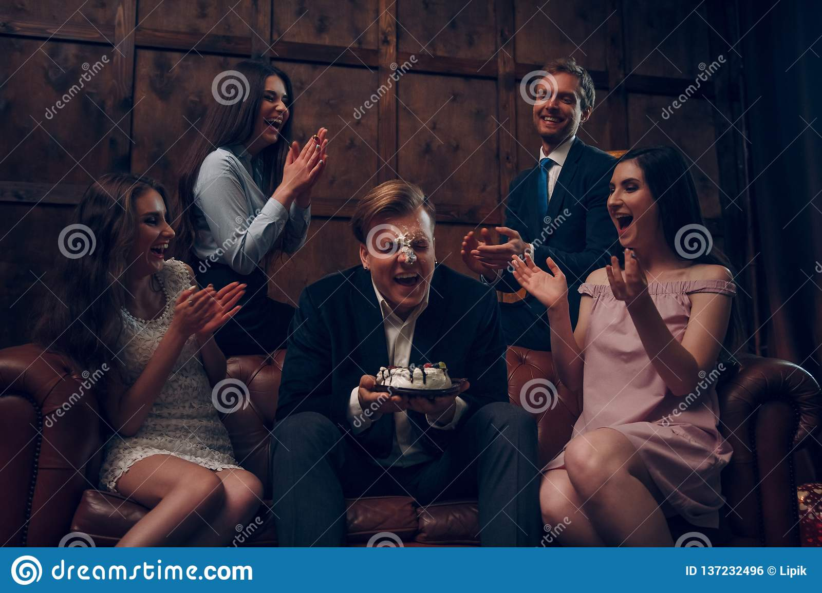 Handsome man`s face covered in birthday cake