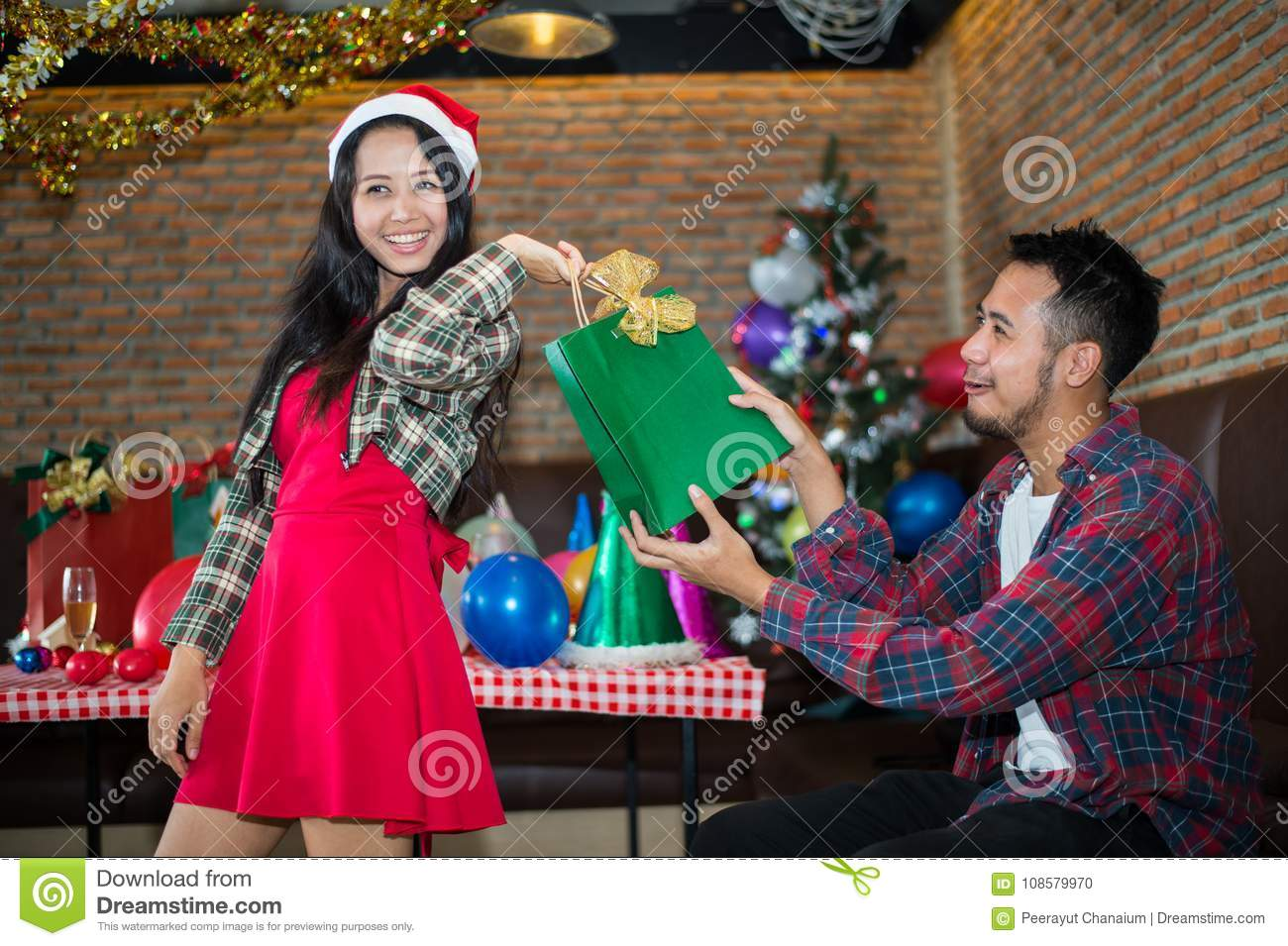 Handsome man sent green gift bag to beautiful woman, who wear red dress and santa claus hat at the party.