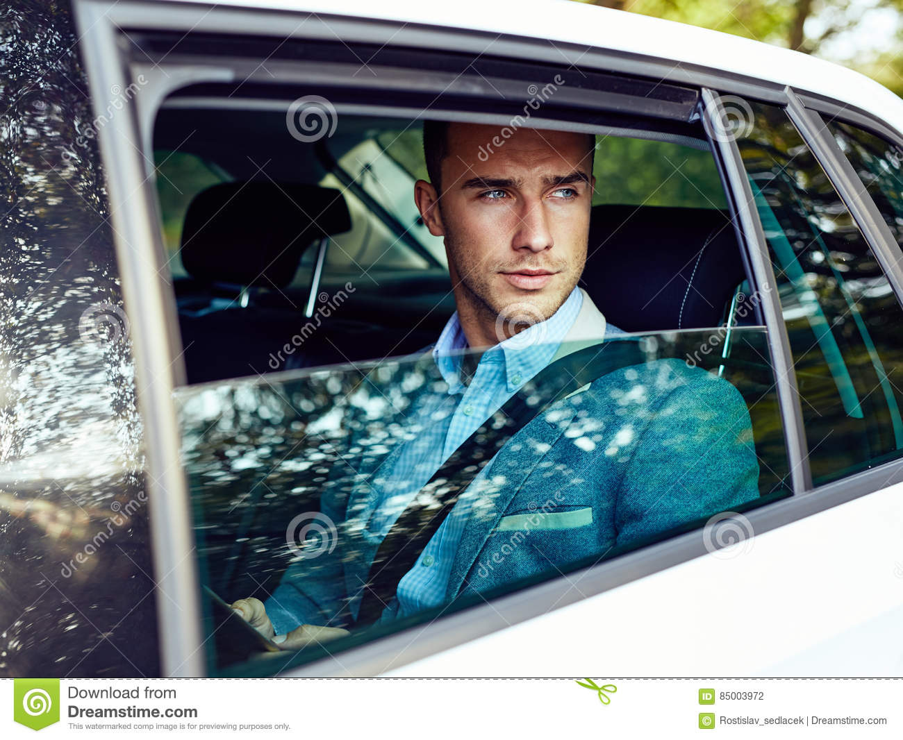 Handsome man sitting in a car with tablet computer