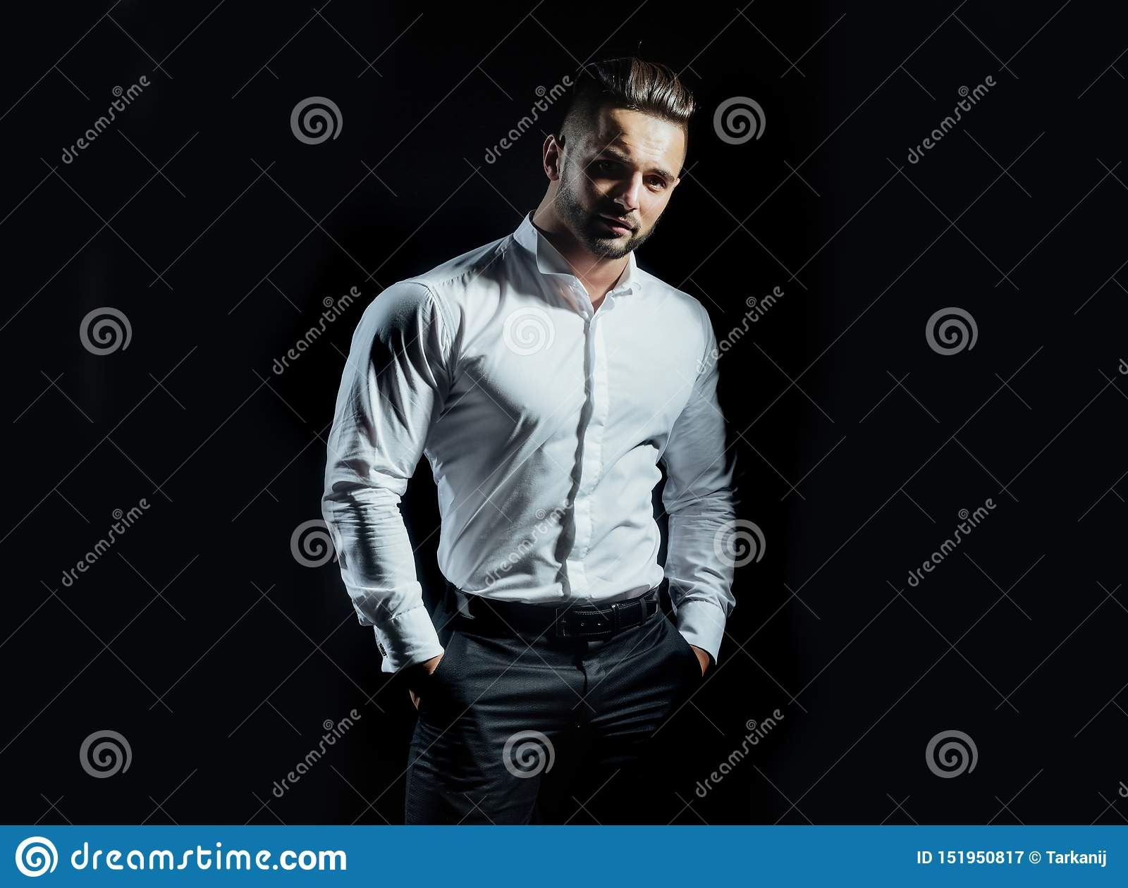 Handsome man standing with arms in pockets isolated on a black background. A handsome confident young man standing and