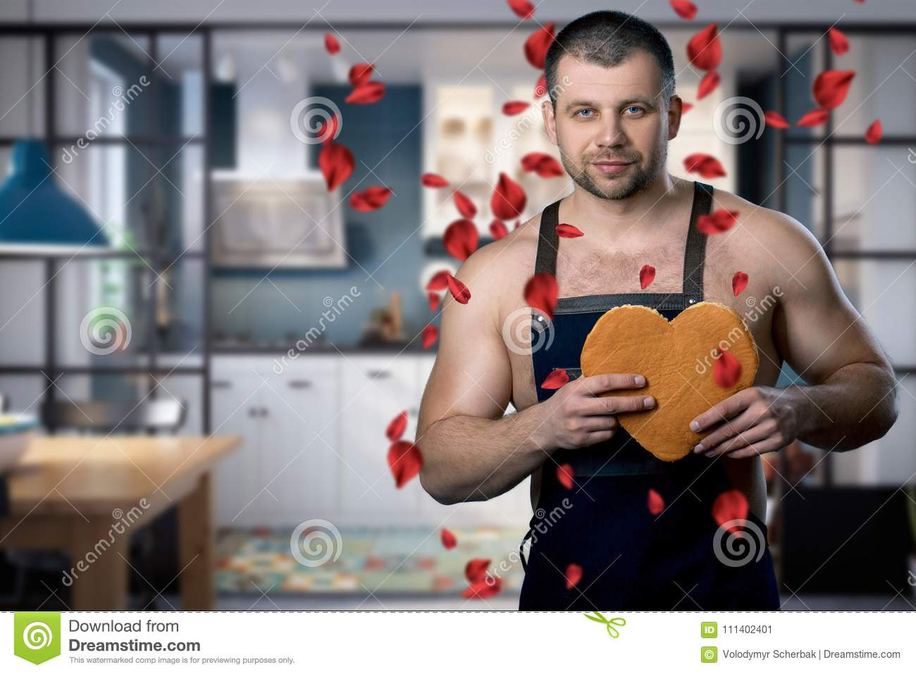 Handsome man standing in the kitchen with a biscuit heart in his hands. rose petals falling on the man. A man is dressed in an apr