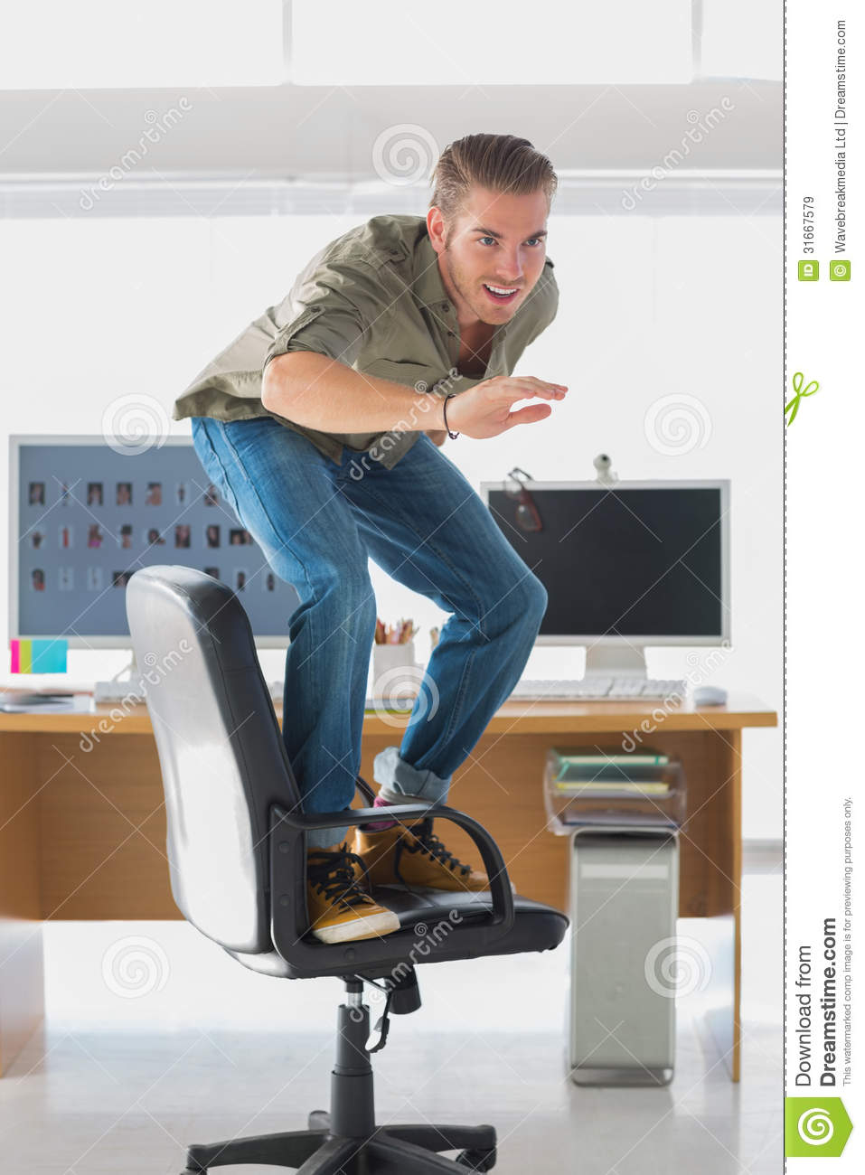 handsome man surfing his office chair royalty free stock