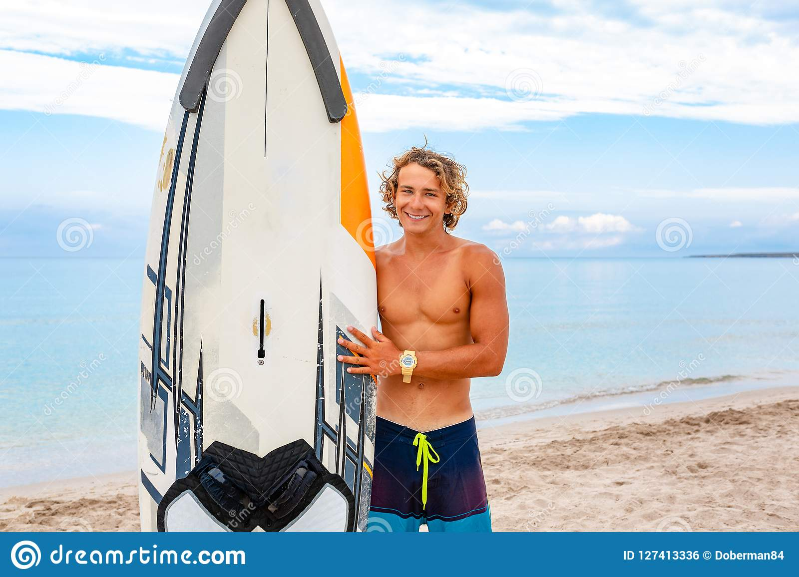 Handsome man walk with white blank surfing board wait for wave to surf spot at sea ocean shore. Concept of sport