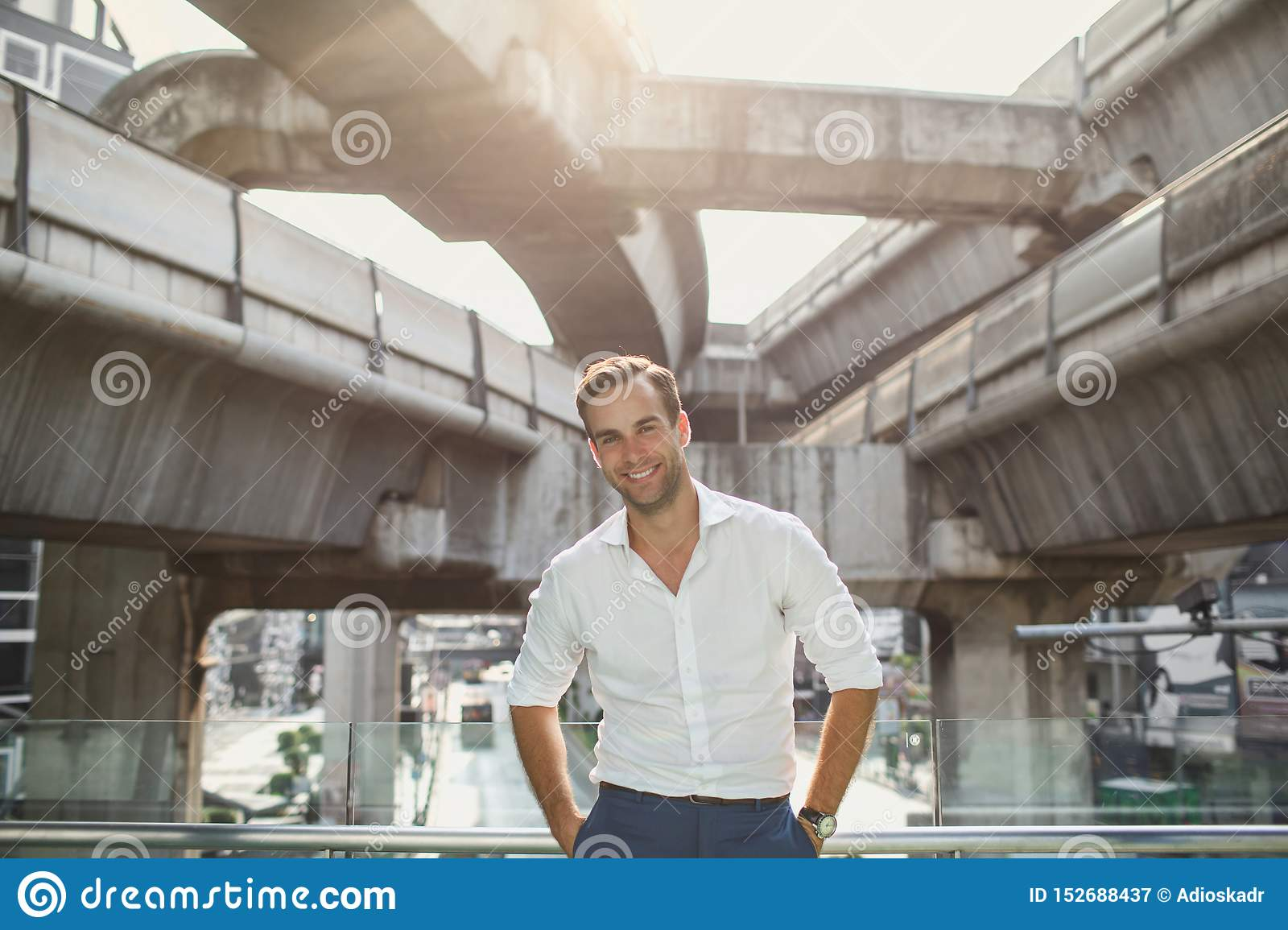 Handsome man in white shirt smiling standing near the mall