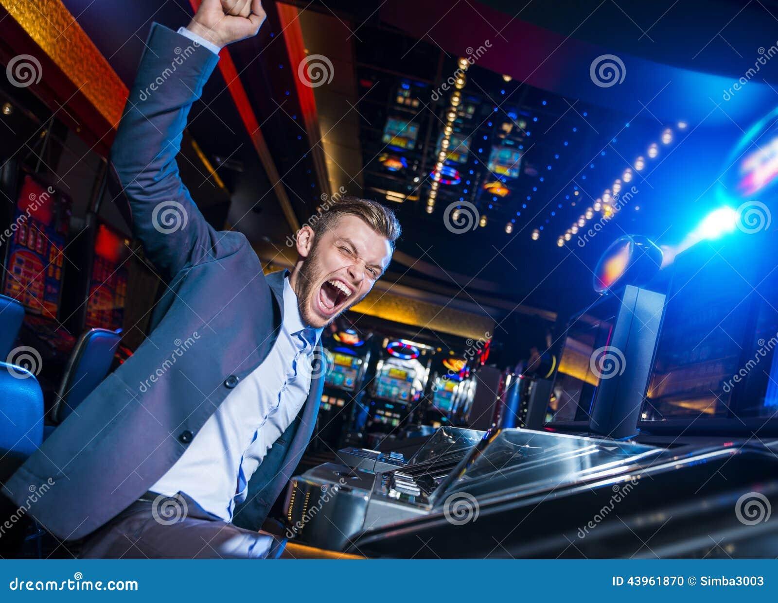 handsome man winning at the slot machine stock photo