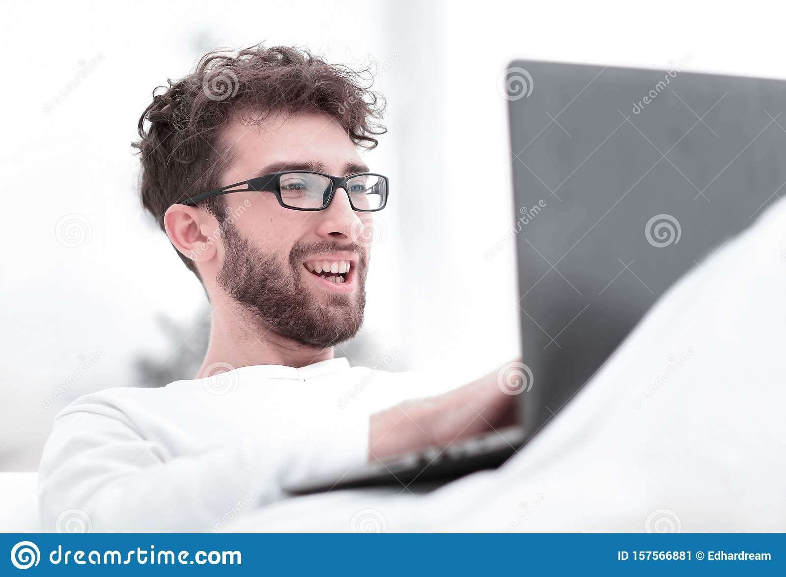 Handsome man working on laptop lying on bed