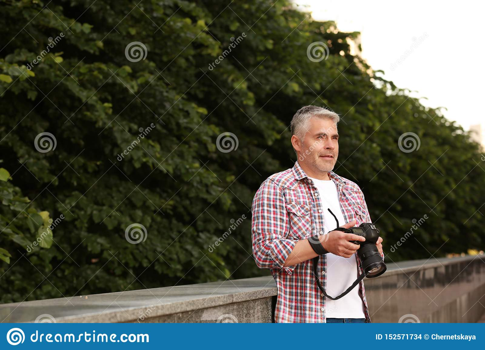 Handsome mature man with professional camera outdoors