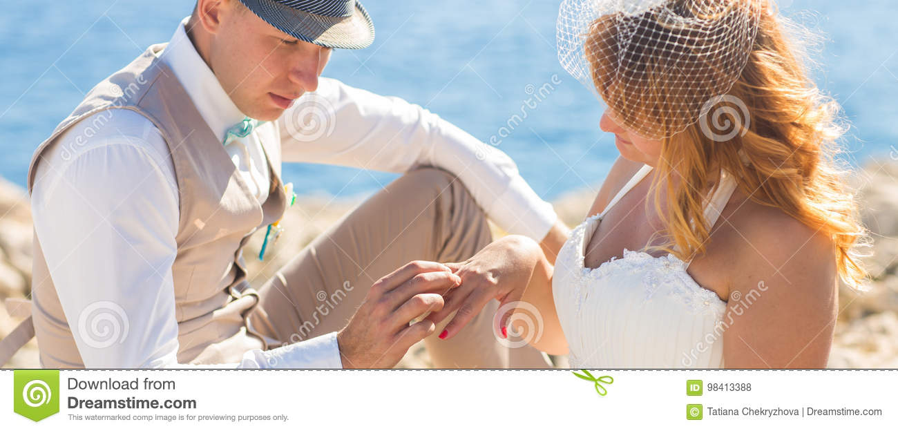 Close-up of Handsome man putting on ring smiling blonde brides finger at the beach