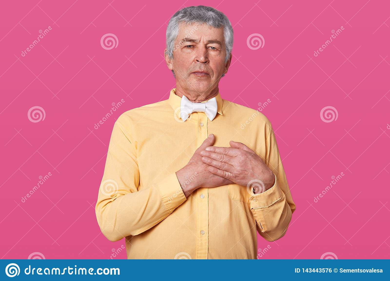 368a4a7078de Handsome middle age hoary senior man wearing yellow shirt and white bow tie  isolated over pink background smiling , stands with hands on chest, ...