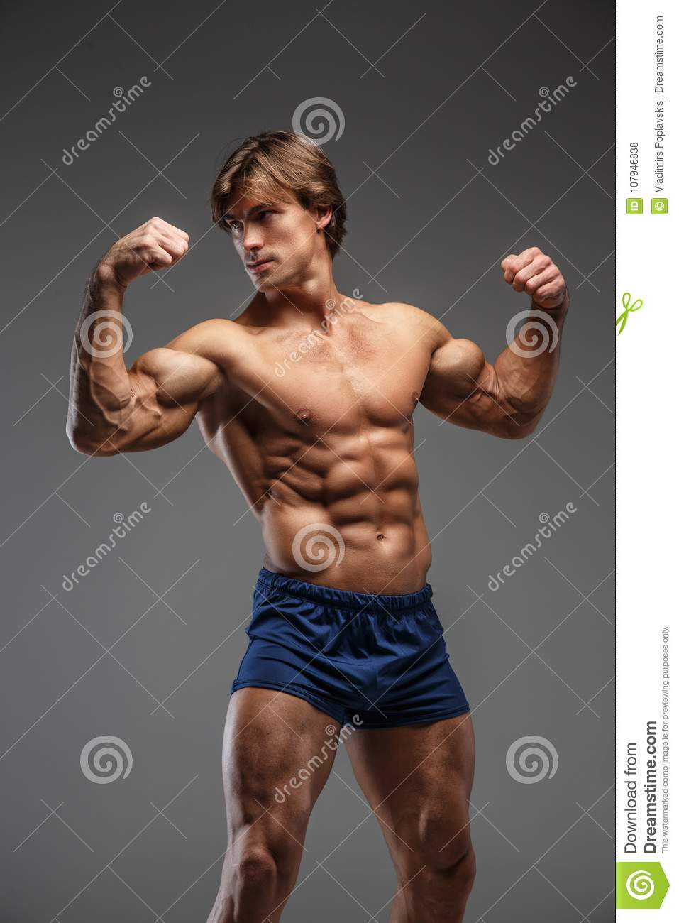 2c0838ce570 Handsome muscular male in blue shorts. Isolated on grey background.
