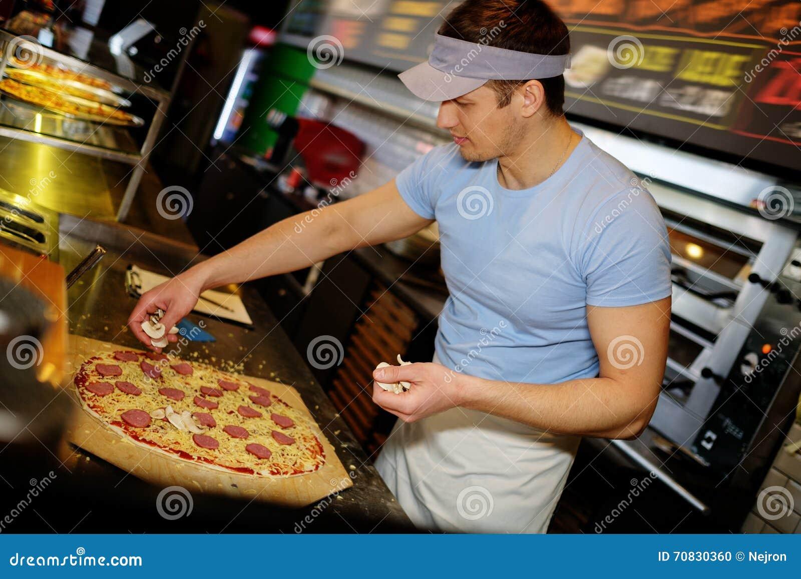 Pizzeria Kitchen handsome pizzaiolo making pizza at kitchen in pizzeria. stock